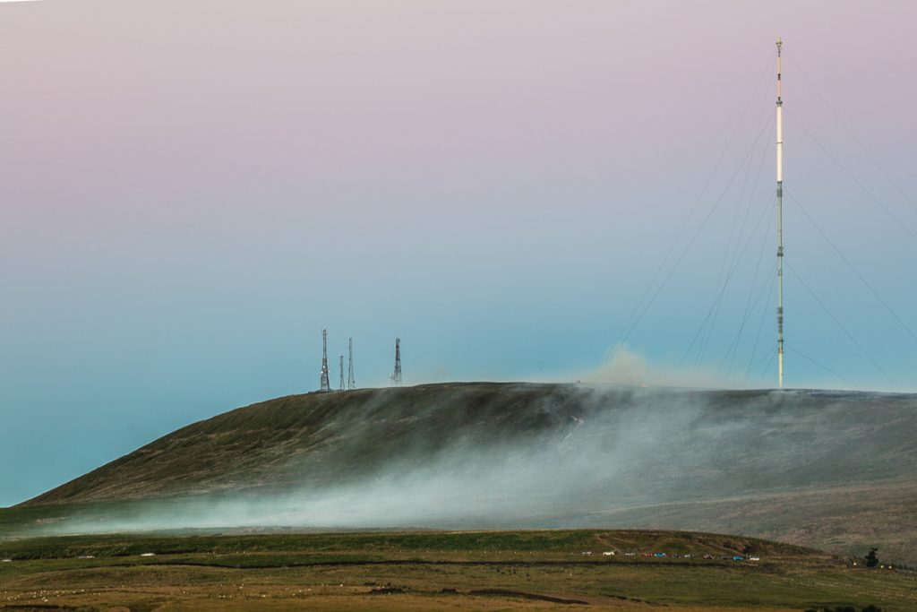 Smoke from a grass fire rolls down the moors beneath the Winter Hill transmission masts.