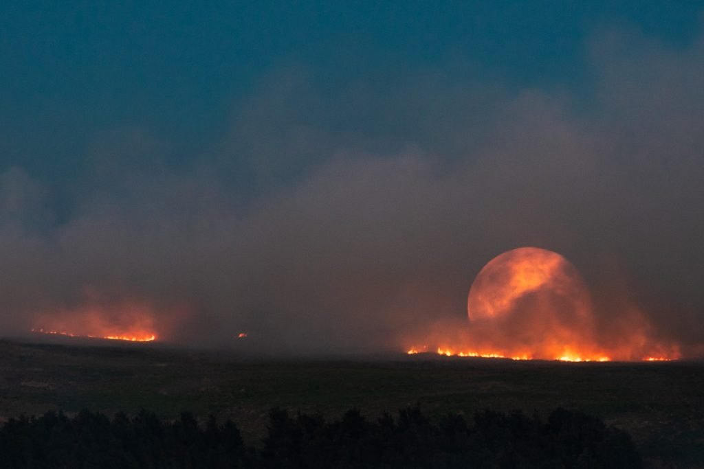 The Full moon rises over moorland fire